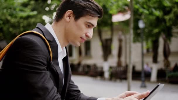 Před kamerou venku uprostřed ulice mladý muž student pomocí elektronického tabletu, aby si nějaké domácí úkoly, zatímco se posaďte na schodech