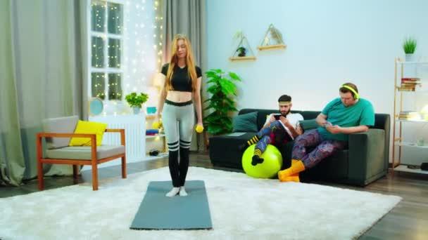 Eine Frau wirft sich in eine Trainingsmatte, hinter ihr sitzen zwei Männer auf der Couch und telefonieren, sie sind alle in einem modernen Raum.