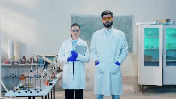 Chemistry laboratory in front of the camera concentrated serious woman and man scientist together looking to the camera posing they wearing protective equipment. Shot on ARRI Alexa Mini.
