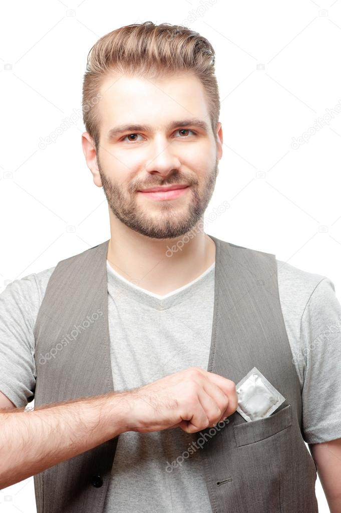 Man Putting A Condom Into Pocket Stock Photo