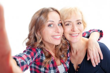 Woman and adult daughter taking selfie