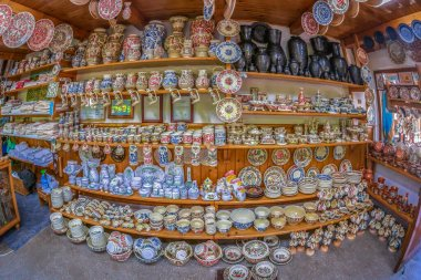 Hungarian traditional ceramic plates from Corund area, Romania, placed ornamentally on a rustic wall at house.