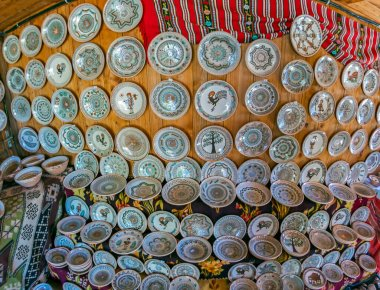 Romanian traditional ceramic plates from Horezu area, Romania, placed ornamentally on a rustic wooden wall at house.