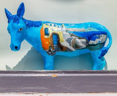 OIA, SANTORINI, GREECE - JUNE 21, 2021: Souvenir ornamental ceramic donkey, with specific drawings from Santorini. The donkey is the ancient means of transport and the symbol of the island.