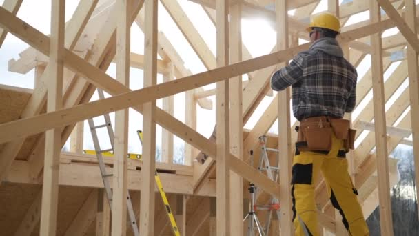 Caucasian Construction Worker Assembling Wooden Beams of Newly Developed Skeleton Frame of the House.