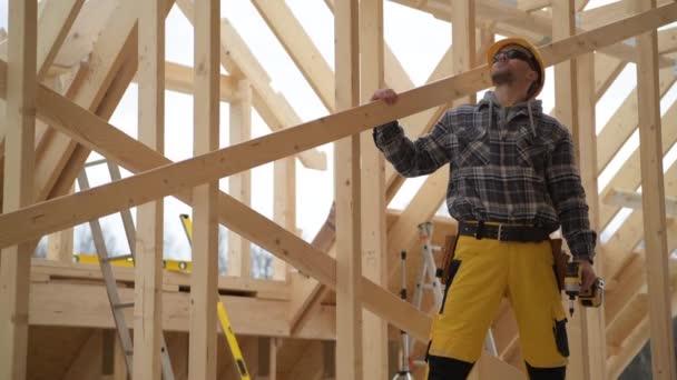 Kaukázusi építőmunkás 40-es éveiben, aki felnéz az újonnan épült ház fából készült csontvázszerkezetének tetőjére.