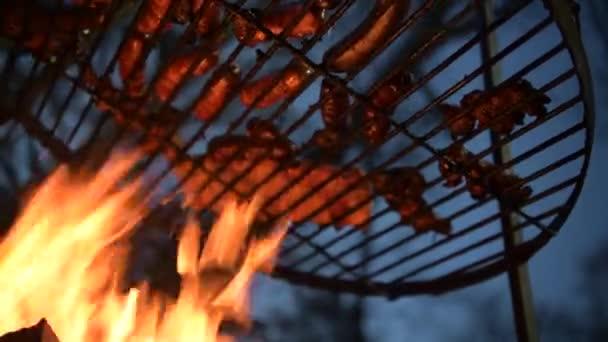 Čas na grilování. Polské klobásy a kusy masa v plamenech