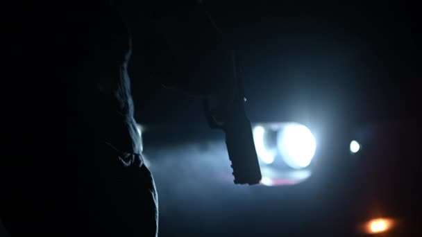 Somebody with Firearm in His Hand in Front of Vehicle at Night