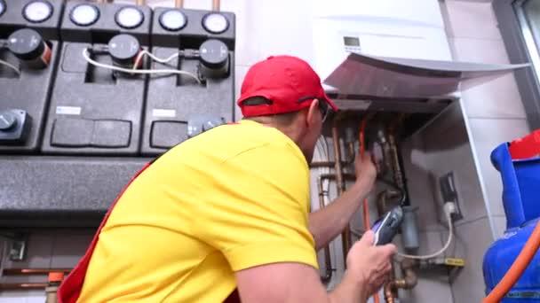 HLK-Arbeiter mit Erdgasdetektor auf der Suche nach einem Leck. Geplante Wartung der Wohnheizung.