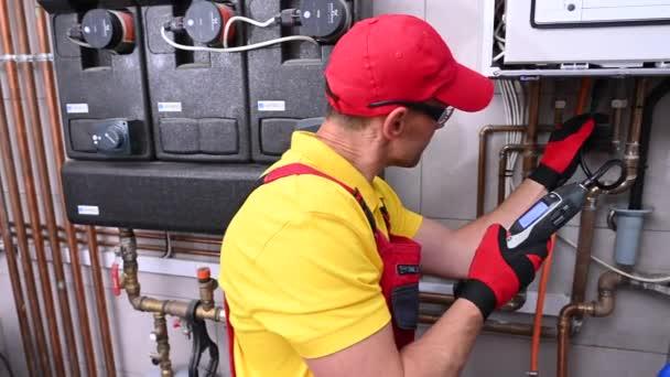 Professioneller Gasheizungstechniker mit Erdgas-Detektorgerät in der Hand auf der Suche nach möglichen Lecks im Heizungssystem.