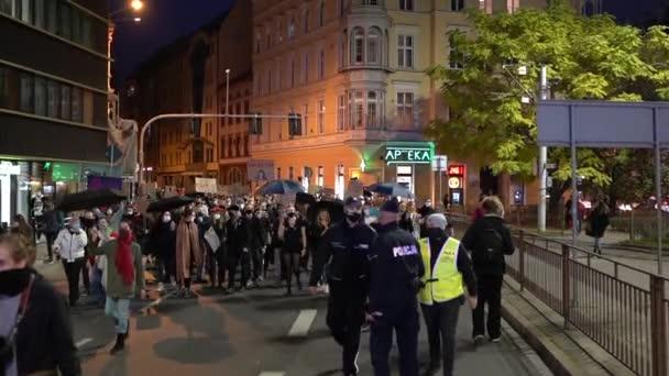 Vratislav, Polsko, 26. října 2020 - Polské ženy stávkují. Po ulicích města se s deštníky pohybuje velký dav lidí, mnoho tisíc pochodů. Maskovaní policejní eskortní demonstranti