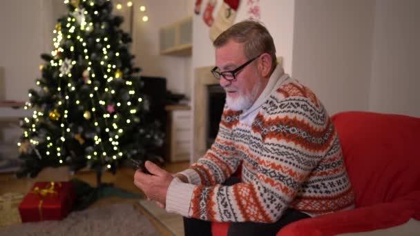 Der alte Mann mit dem Smartphone telefoniert in der Nähe des Weihnachtsbaums
