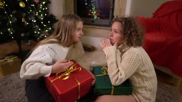 Dvě školačky sedí u zdobeného vánočního stromku a drží krabice s dárky. Děvčata si spolu živě povídají. Dárek od Santy