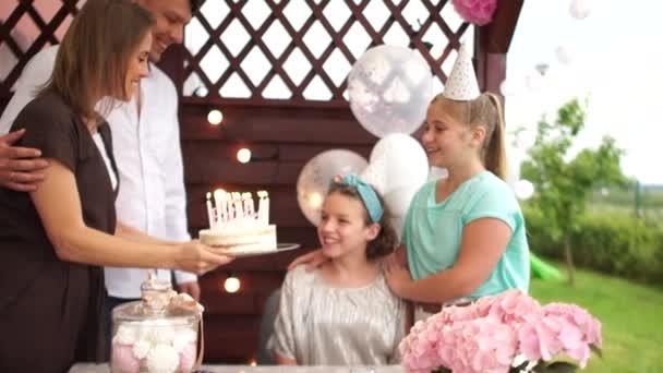Teenager Mädchen feiert ihren Geburtstag mit Familie, die die Kerzen auf ihrem Kuchen ausbläst. Geburtstagstorte und glückliche Familie