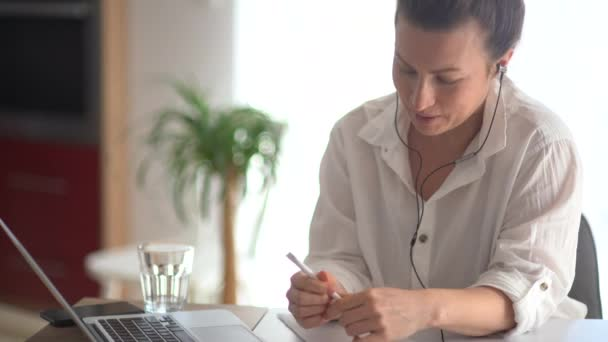 Egy fehér inges hölgy laptopot és vezetékes fejhallgatót használ, mikrofonnal a kezében beszél, jegyzetel egy jegyzetfüzetben. A komoly üzletasszony videóhívást tart az irodában.