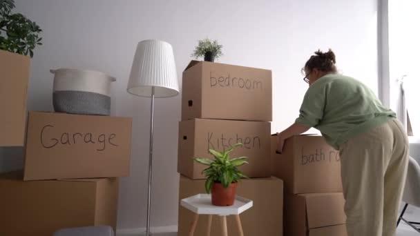 Mladá žena sbírá věci na stěhování. Nový dům, pronájem nemovitostí. Krabice s nápisy koupelna, garáž, obývací pokoj a kuchyň