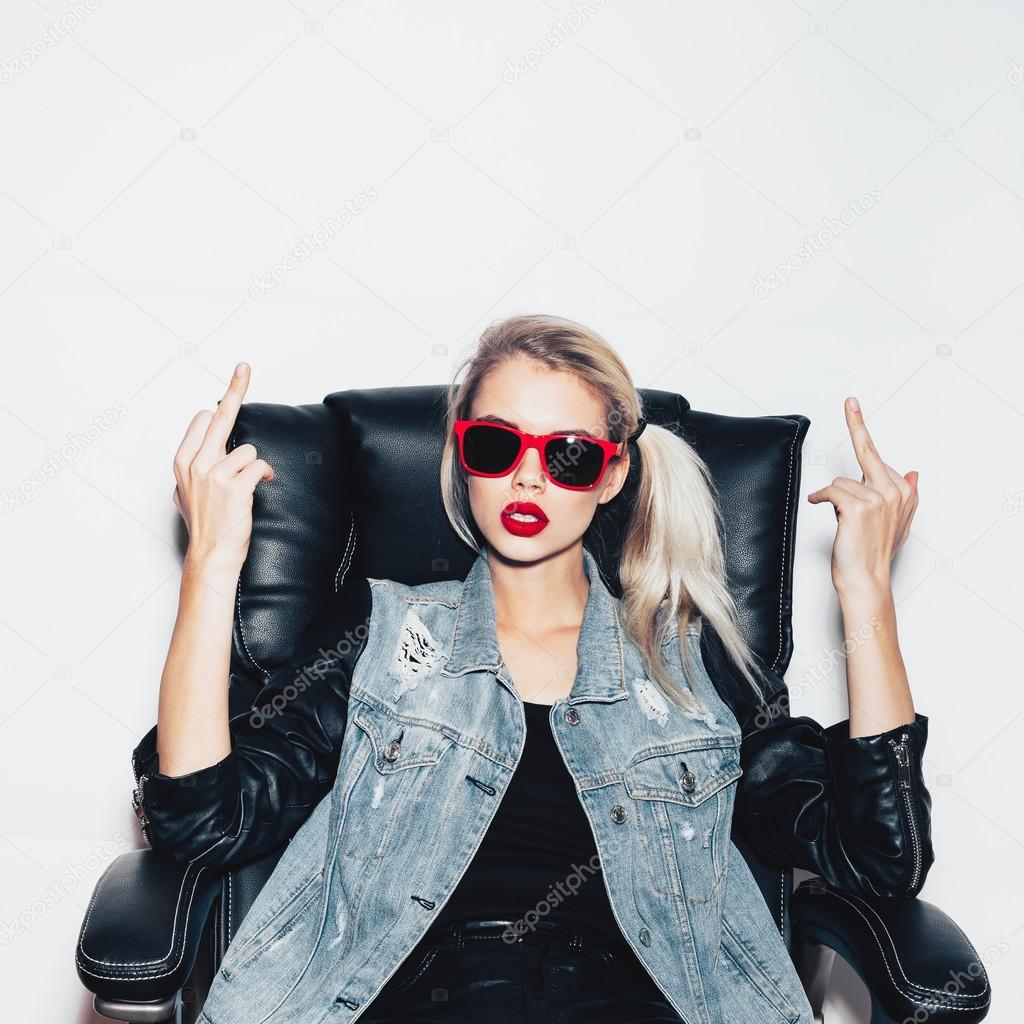 3f9cb70f5ed86 Jeune femme blonde à lunettes de soleil s asseoir sur la chaise de bureau  noir et montrant le doigt du milieu– images de stock libres de droits