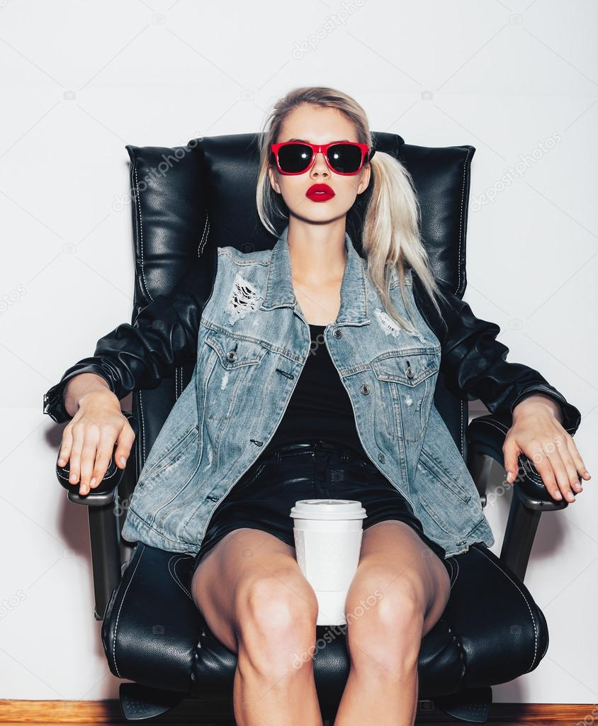 a8e57c47aff8f Sexy blonde woman in sunglasses sit on black office chair and holding a cup  of coffee knees. Fashion hipster girl. White background