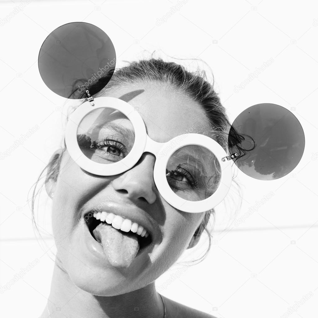 be59e61ecfef8 Jeune fille dans la liste langue de lunettes de soleil– images de stock  libres de droits