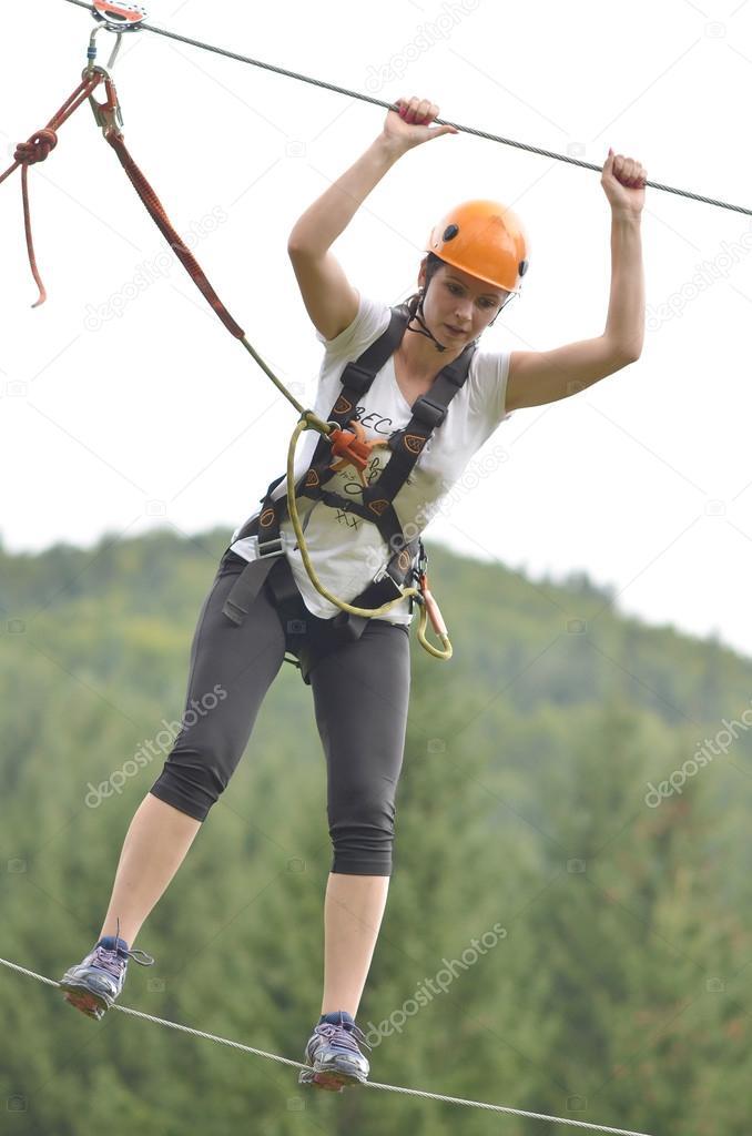 Happy girl climbing between trees