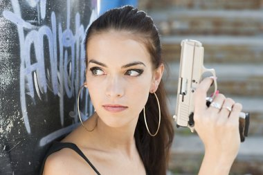 Beautiful woman with gun outdoors stock vector