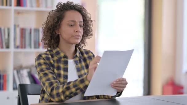 Junge Frau mit gemischter Rasse liest bei der Arbeit Dokumente