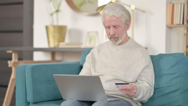 Online-Shopping-Erfolg von Senioren auf dem Sofa am Laptop