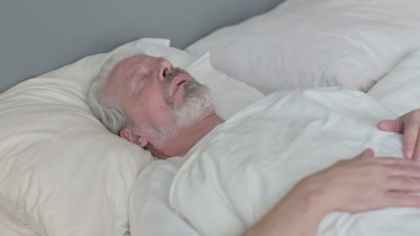 Békés öregember alszik az ágyban.