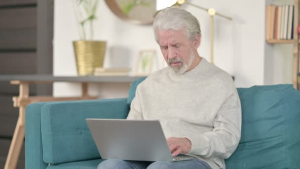 Älterer Mann mit Laptop hat Handgelenkschmerzen auf Sofa