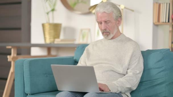 Schöner Senior alter Mann mit Laptop auf Sofa
