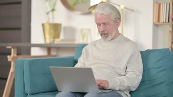 Erfolgreicher Senior mit Laptop feiert auf Sofa