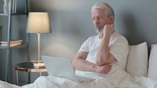 Alter Mann mit Laptop im Bett