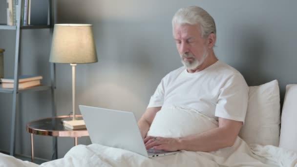 Laptop-Arbeit eines alten Mannes mit Nackenschmerzen im Bett