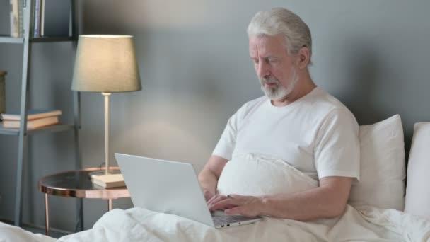 Alter Mann mit Laptop reagiert auf Versagen im Bett