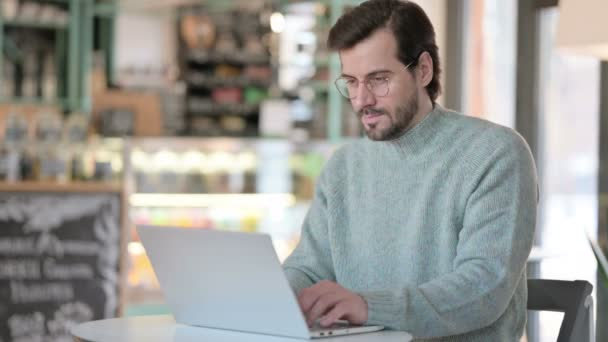 Young Man with Laptop showing No Sign by Finger in Cafe