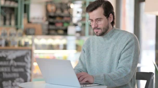 Palce nahoru od mladého muže s notebookem v kavárně