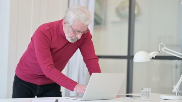 Kreativer alter Mann steht und arbeitet am Laptop