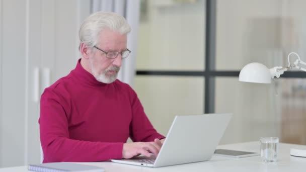 Daumen runter vom kreativen alten Mann mit Laptop bei der Arbeit