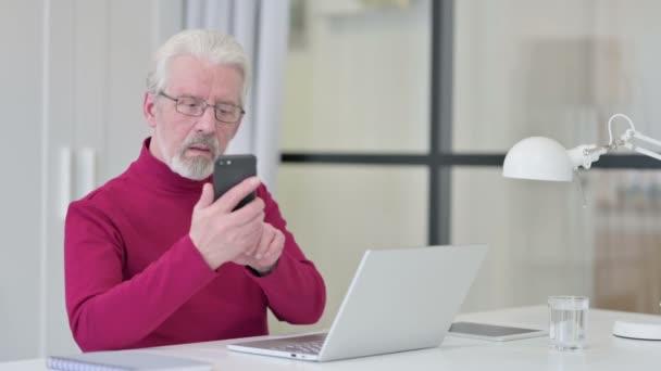 Kreativer alter Mann mit Laptop im Smartphone-Gespräch