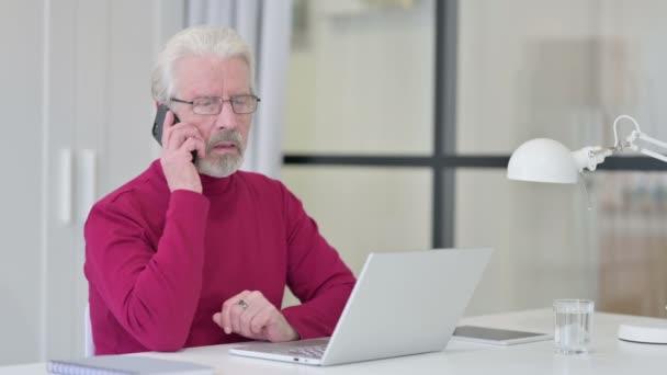 Kreativer alter Mann mit Laptop wütend auf Smartphone