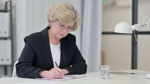 Alte Geschäftsfrau schreibt bei der Arbeit auf Papier