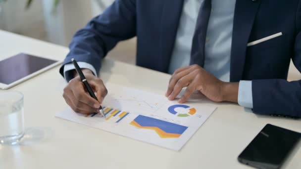 Afrikanischer Geschäftsmann liest Charts auf Papier, Papierkram