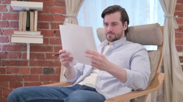 Nenucený mladý muž čte dokumenty na pohovce