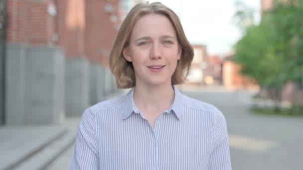 Porträt einer Frau, die auf die Kamera zeigt