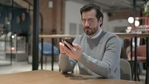 Attraktiver junger Mann mit Smartphone im Büro