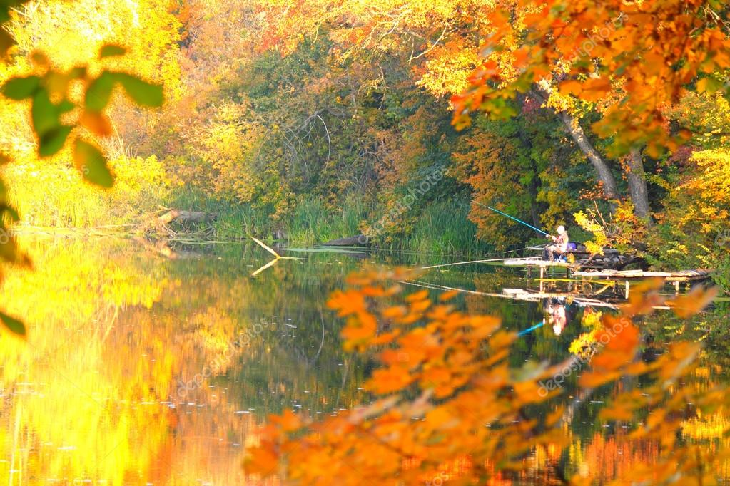 Beautiful bright autumn landscape with trees and a fisherman on a river