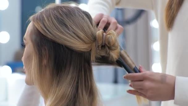 Mladá brunetka žena kadeřnice dělá styling na dlouhé vlasy blondýny