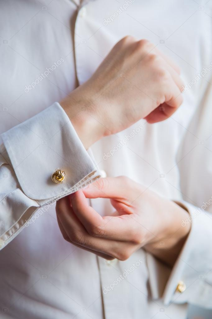 9f6292dba643 Τα χέρια του νεαρού κινηματογράφηση σε πρώτο πλάνο. Το φοράει ένα άσπρο  πουκάμισο. Με το ένα χέρι ο άνθρωπος ρυθμίζει του cufflink στην περιχειρίδα  — Εικόνα ...