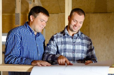 Two builders discussing a building plan