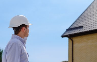 Engineer, architect or building inspector standing in his hardhat checking a roof on a new build house against a blue sky stock vector